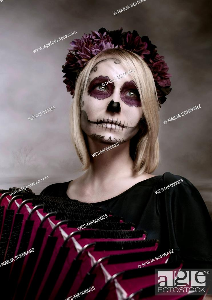 Stock Photo: Portrait of woman with sugar skull makeup and accordion.