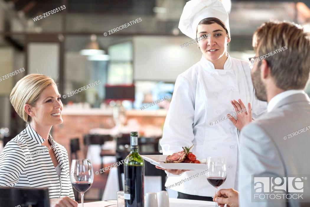 Stock Photo: Chef serving food for mid adult couple.