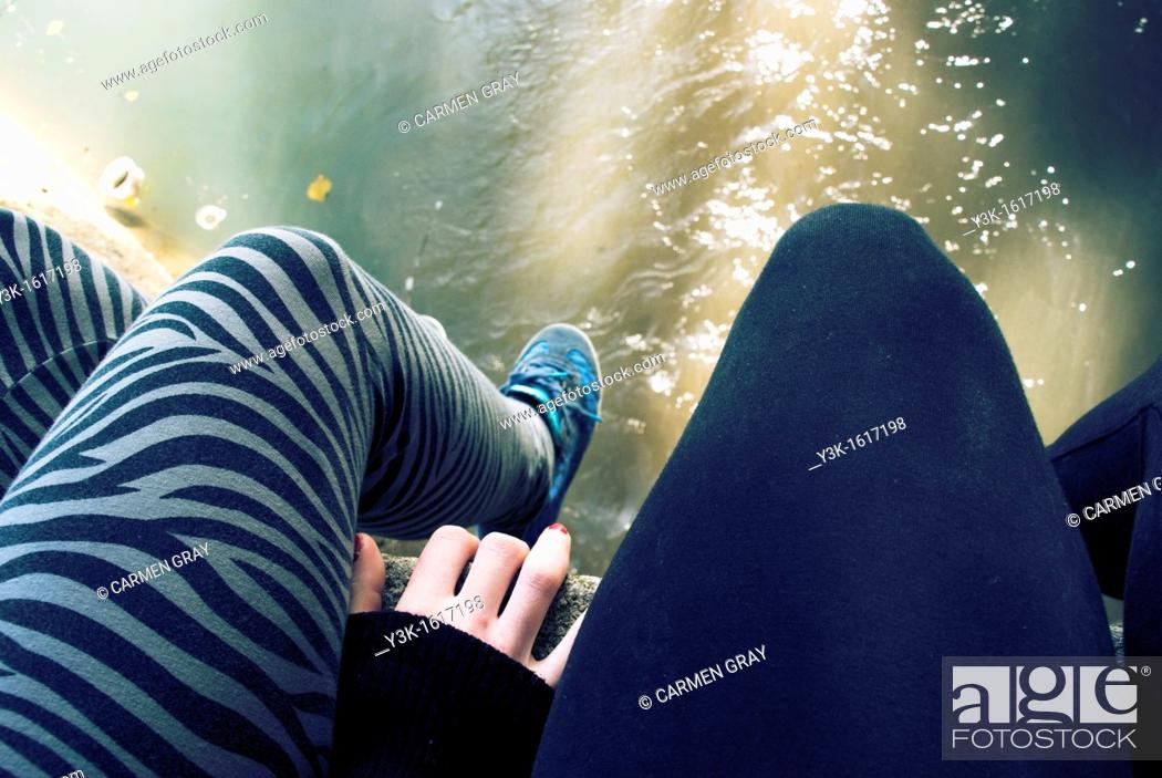 Stock Photo: Legs of two girls sitting in the bank of a river, Ayora, Valencia, Spain.