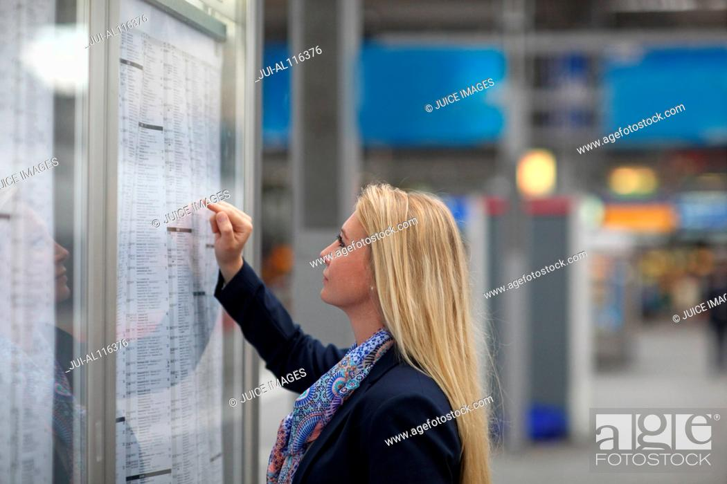 Photo de stock: Mid adult woman studying train timetable, Munich, Bavaria, Germany, Europe.
