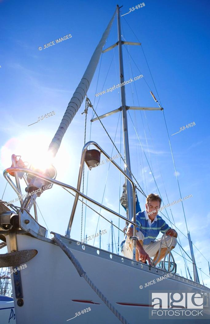 Stock Photo: Man crouching on deck of moored sailing boat, holding rope lens flare.