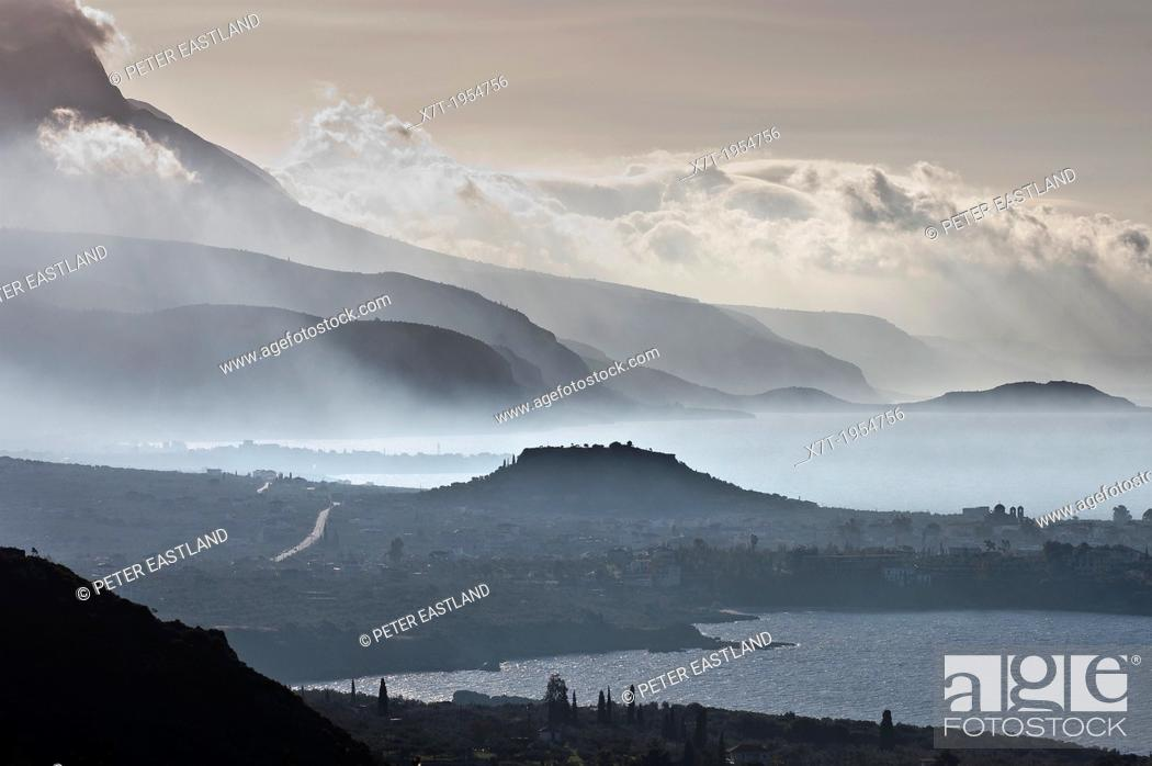 Stock Photo: Looking south down the Messinian coast of the outer Mani on a misty morning with. The seaside town of Stoupa and the prominent mound of its ancient acropolis is.