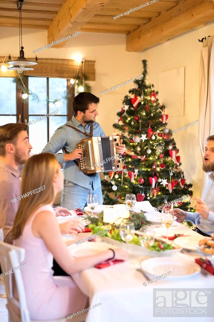 Imagen: Young man playing accordion at Christmas dinner table.