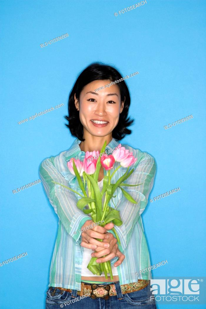 Stock Photo: Woman holding flowers.