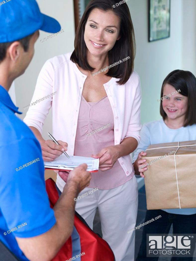 Stock Photo: Male delivery person giving package to woman.