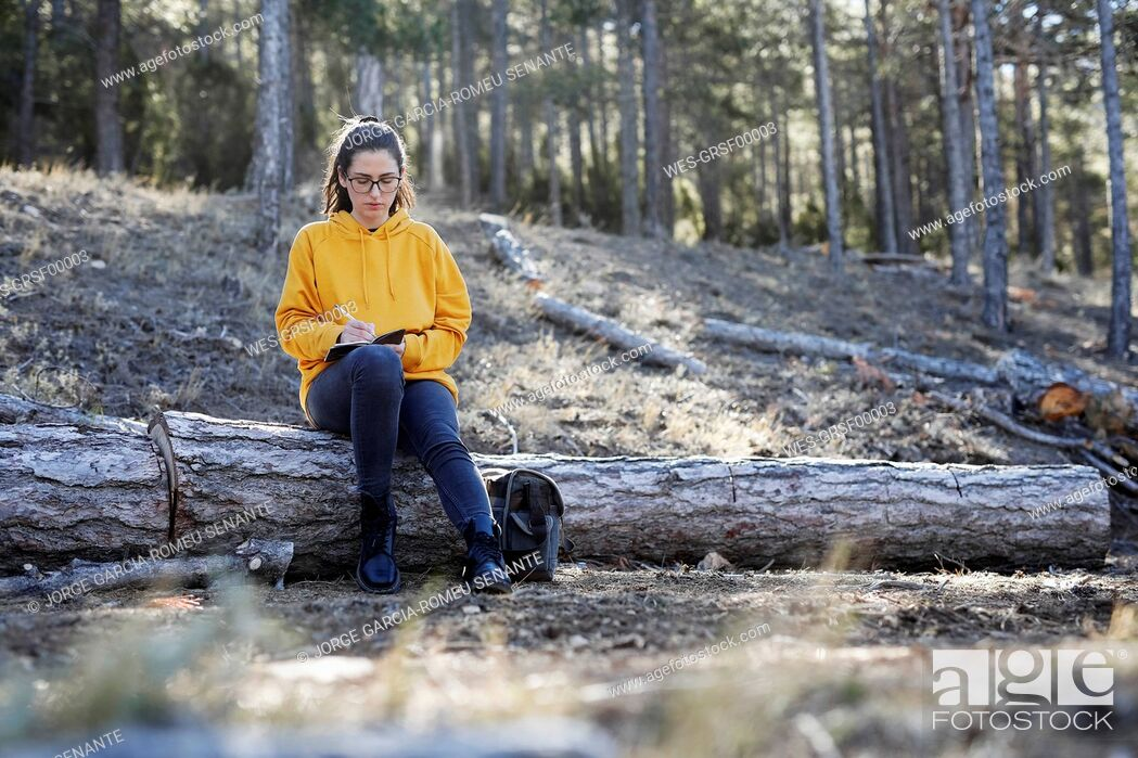 Stock Photo: Young woman with yellow sweater in the forest, writing.