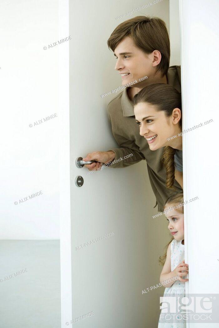 Stock Photo: Family peeking in doorway.