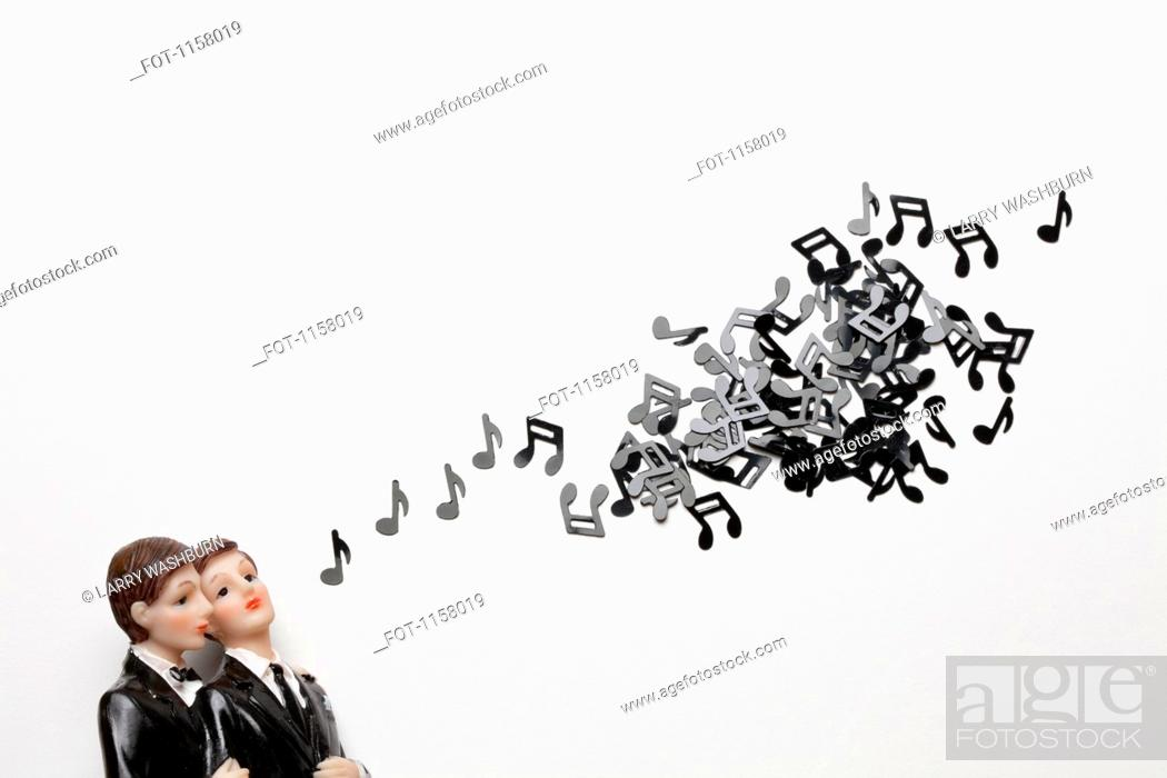 Stock Photo: Two male figurines next to a group of musical notes.