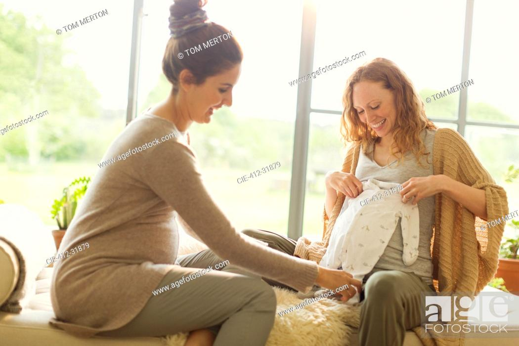 Stock Photo: Pregnant women looking at baby clothing.