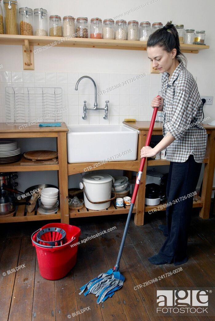 Imagen: Woman mopping wooden floor.