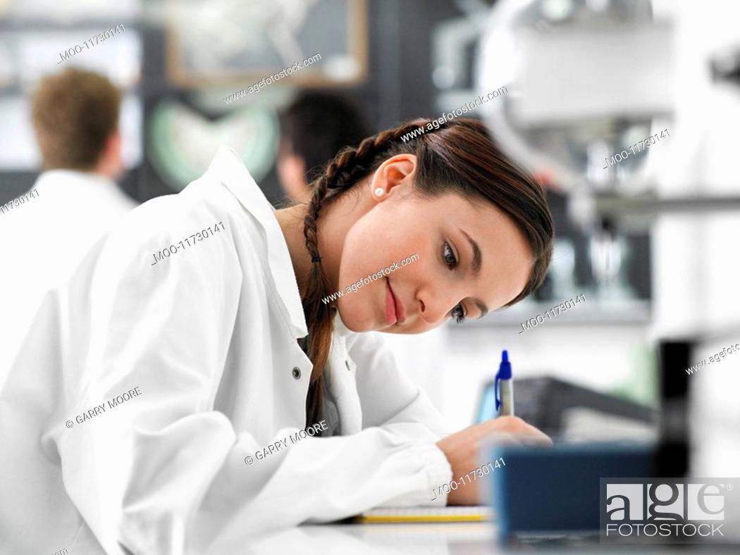 Stock Photo: Teenager writing in science class.