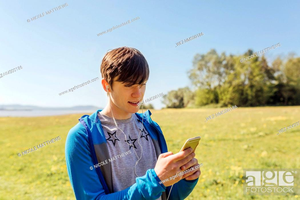 Imagen: Portrait of young man hiking, listening to music.