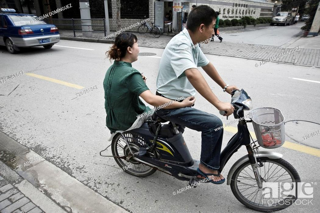 Stock Photo: a man leads a woman in the bike. Shanghai, China.