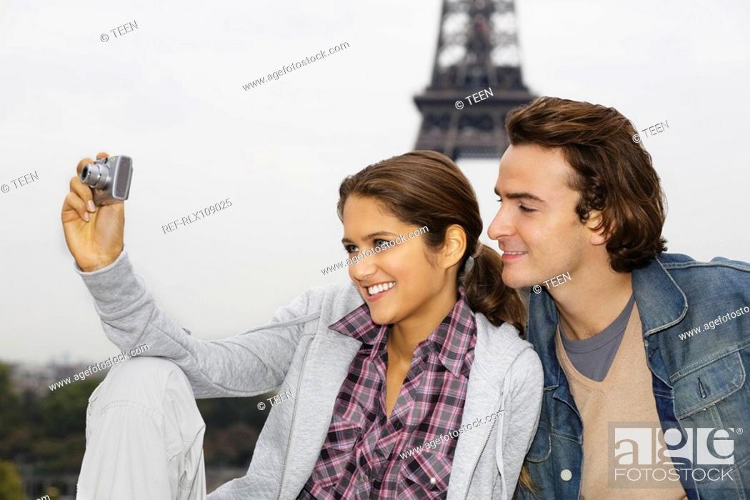 Stock Photo: Young couple, woman taking photo with digital camera, Eiffel tower in background.