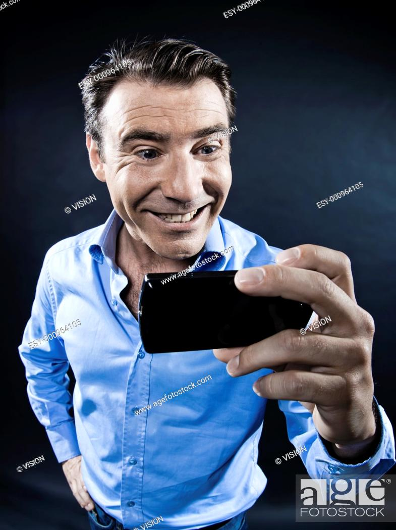 Stock Photo: caucasian man toothy smile holding cellphone portrait isolated studio on black background.