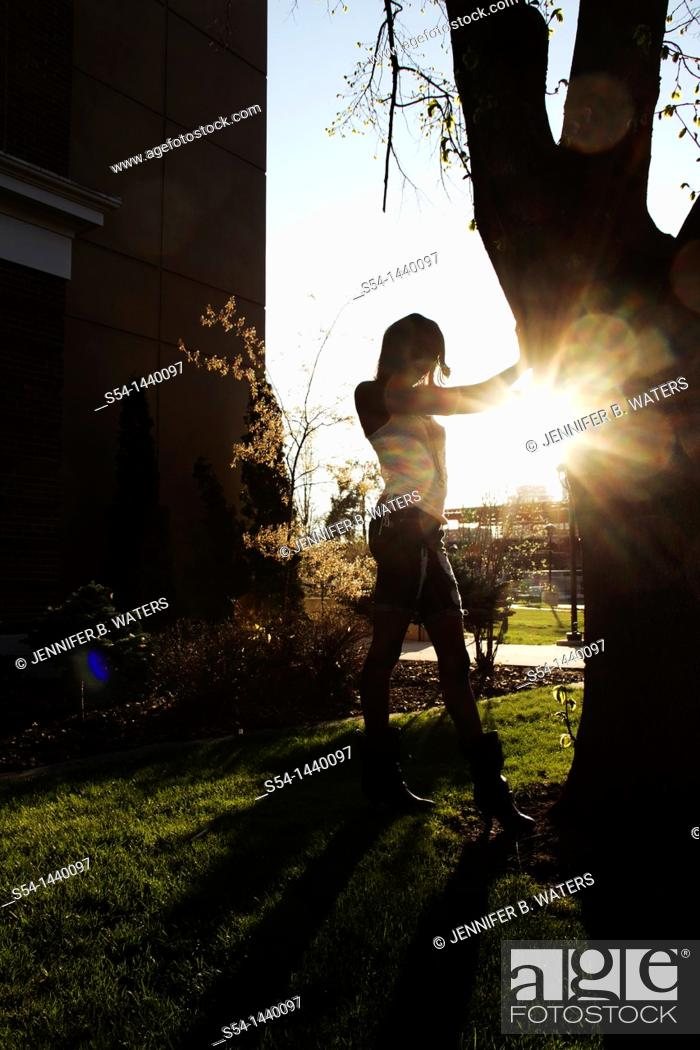 Stock Photo: A young woman standing by a tree, backlit by the sun.