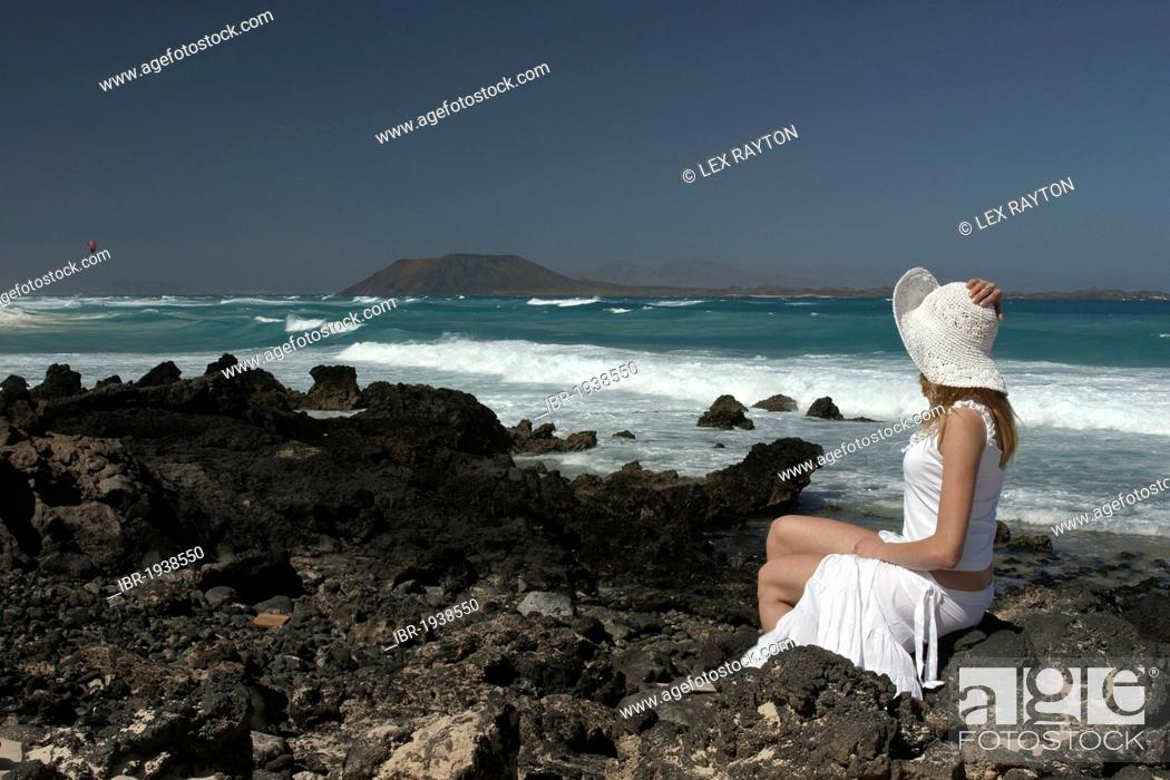 Stock Photo: Woman on a rocky beach, Corralejo, Fuerteventura, Lanzarote in the back, Canary Islands, Spain, Europe.