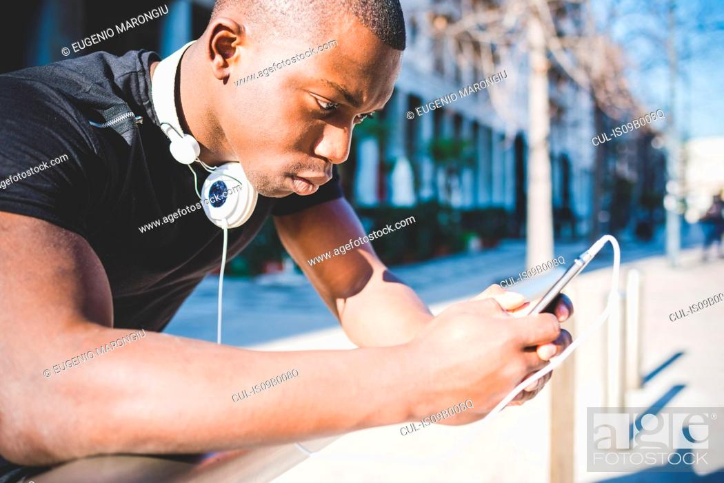 Stock Photo: Young man, outdoors, holding smartphone, headphones around neck.