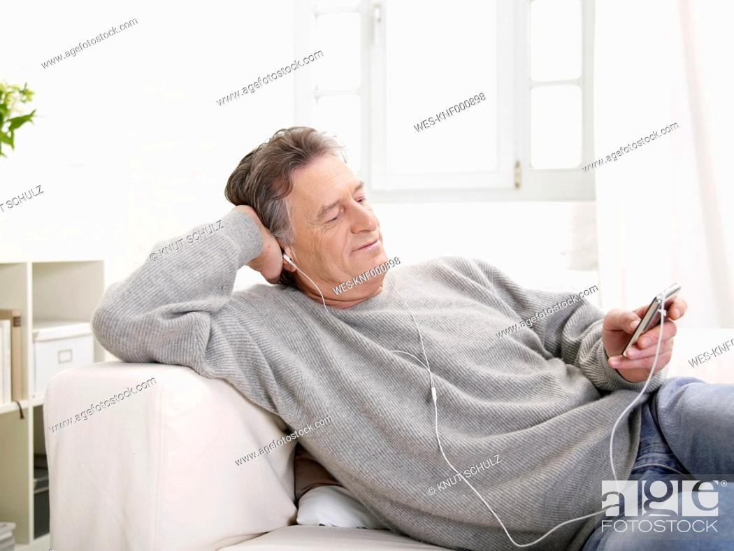 Stock Photo: Germany, Hamburg, Senior man listening MP3 player.