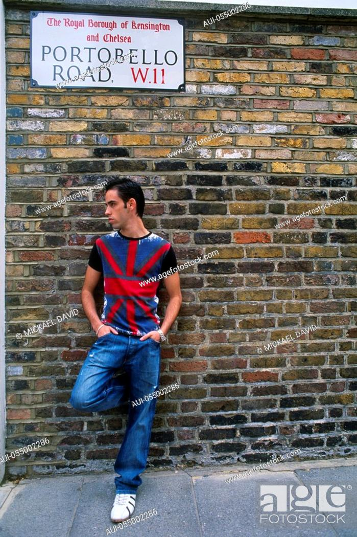 Stock Photo: England - London - Notting Hill district - Portobello Road - young man leaning against brick wall.