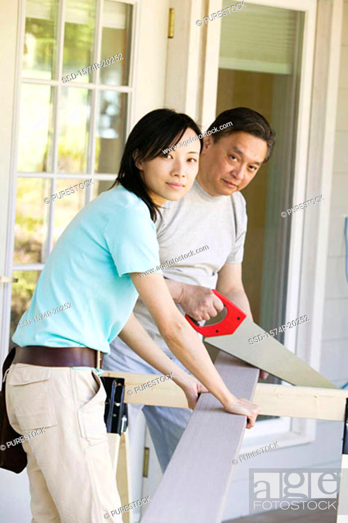 Stock Photo: Mid adult man cutting a plank with a saw.