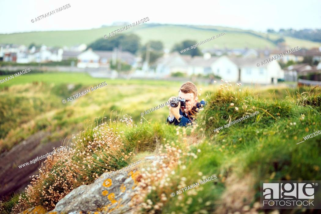 Stock Photo: Man photographing on grassy hill.