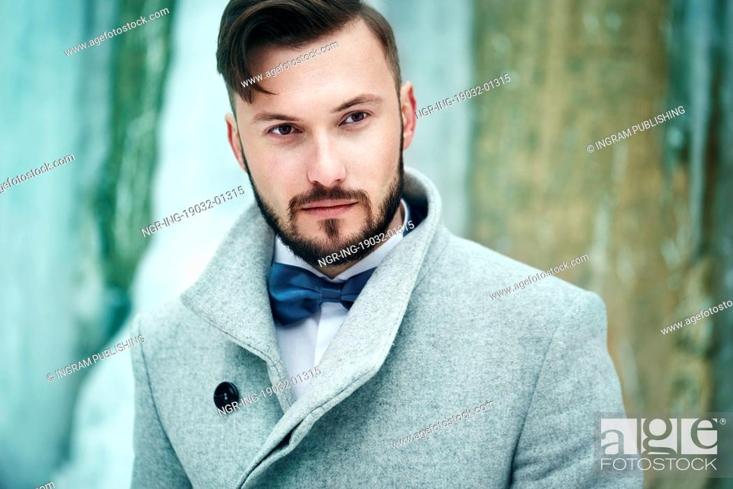Outdoor portrait of handsome man in gray coat. Fashion photo