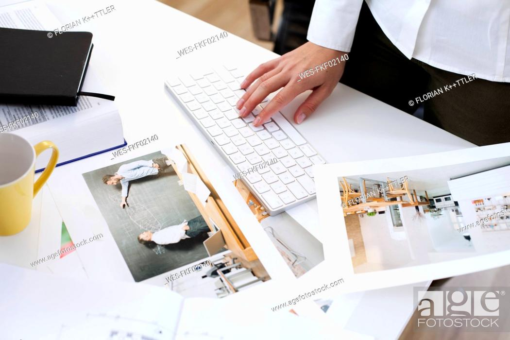Stock Photo: Close-up of woman holding photography and using computer keyboard in office.