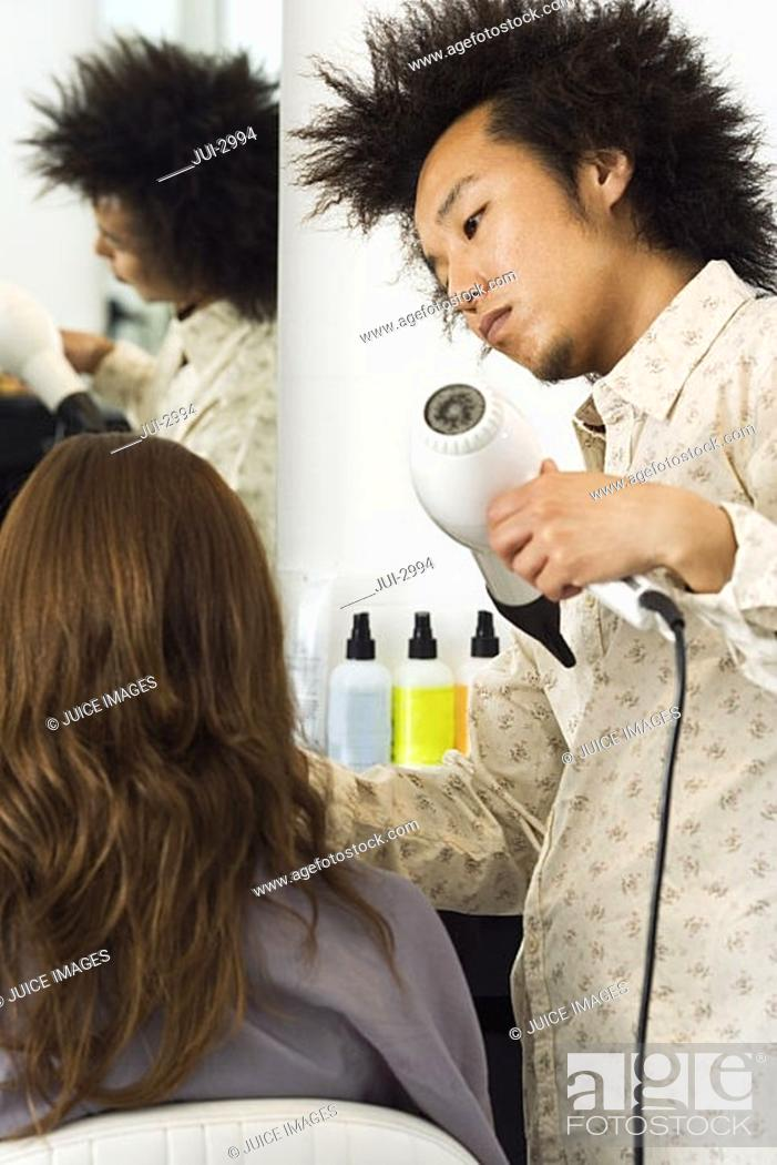 Stock Photo: Young male hairdresser blow-drying woman's hair with hair dryer in salon, rear view.