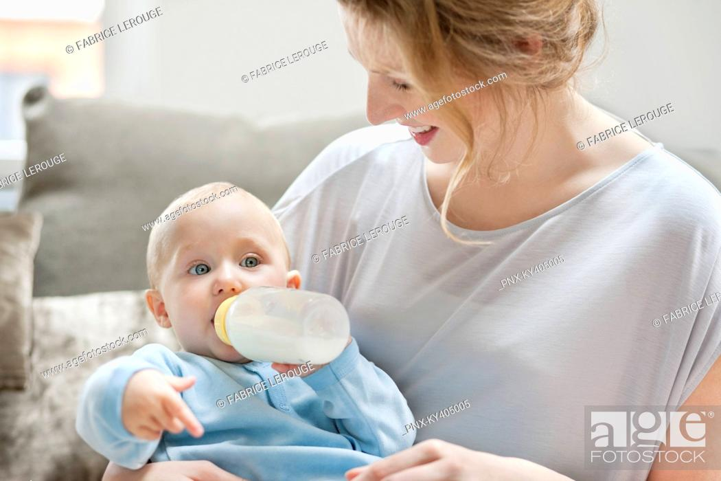 Stock Photo: Baby girl feeding on milk with a milk bottle.