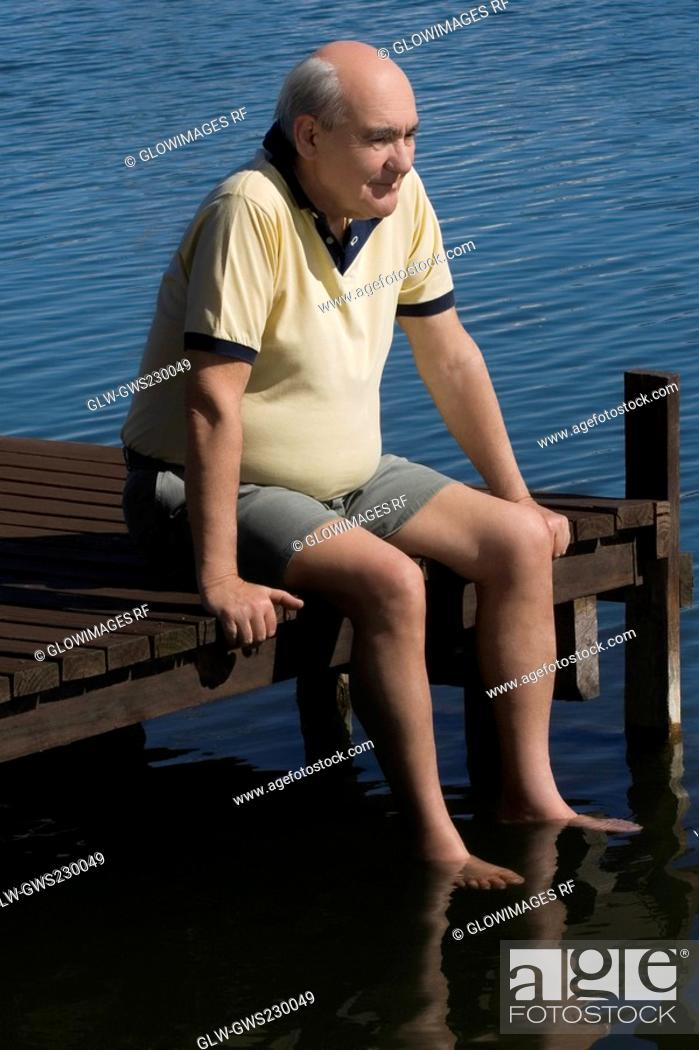 Stock Photo: Senior man sitting on a boardwalk.