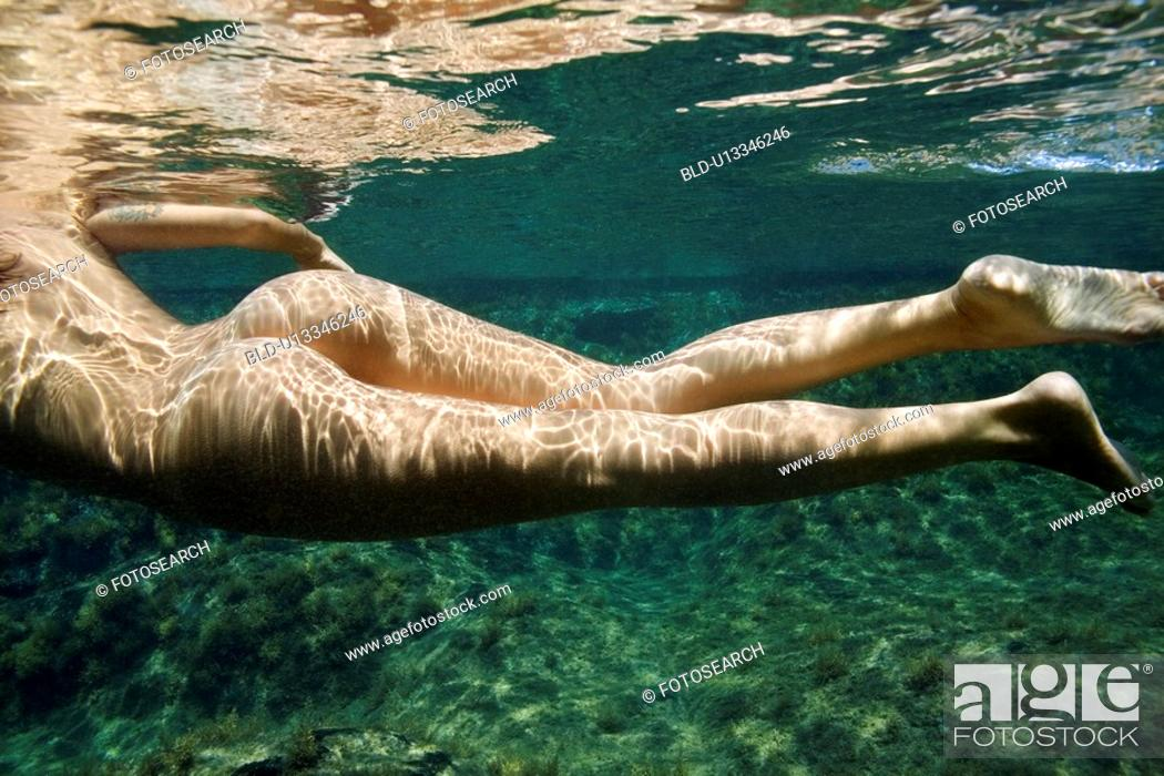 Stock Photo: Caucasian young nude female body swimming underwater.