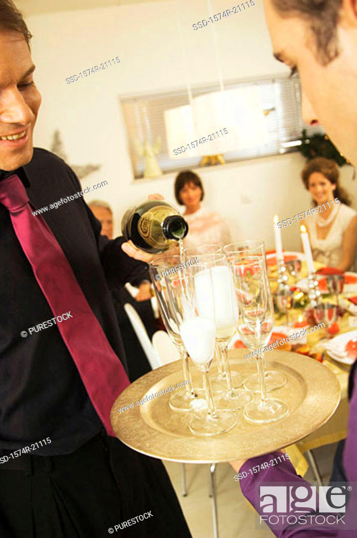 Stock Photo: Close-up of a mid adult man pouring champagne into champagne flutes.