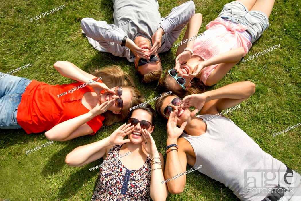 Photo de stock: friendship, leisure, summer and people concept - group of smiling friends lying on grass in circle outdoors.