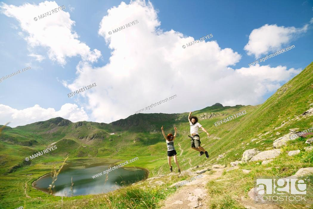 Stock Photo: Young couple jumping in a big valley with glacial lake on background, in Ordesa, Huesca, concept of freedom.