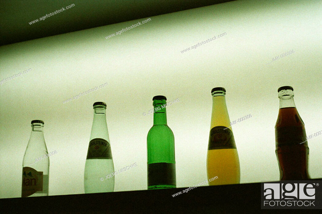 Stock Photo: Group of bottles with table water or soda or soft drinks on a board, light in the background.