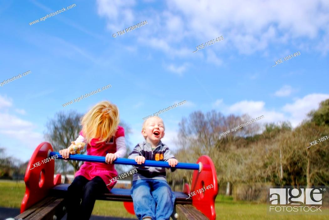 Stock Photo: 7 year girl and 3 year boy playing on seesaw in childrens playground.