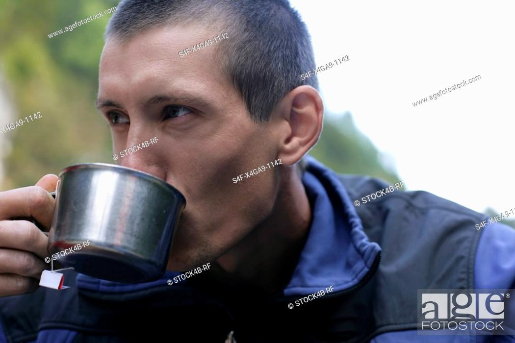 Stock Photo: Young man with a shaved head is drinking from a metallic cup, close-up.