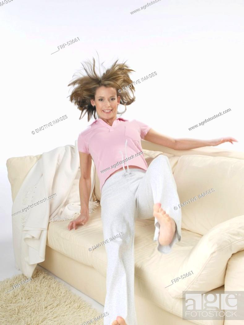 Stock Photo: Woman is jumping onto the sofa.