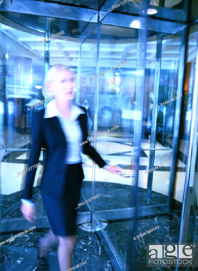 Stock Photo: Businesswoman Walking Through a Revolving Door.