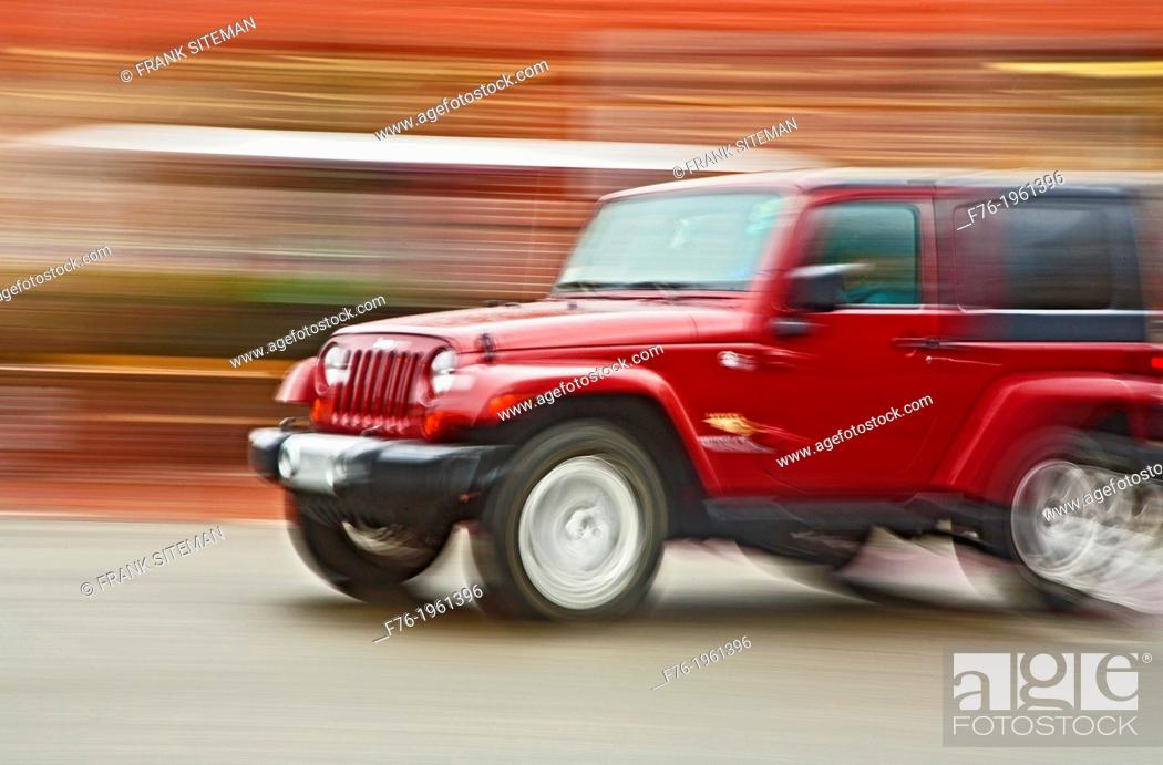 Stock Photo: Panning photograph of a Jeep /SUV in motion, showing a blurred background created by camera movement or a panning technique.