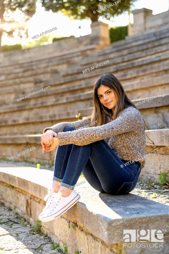 Photo de stock: Portrait of young woman sitting on stairs outdoors.
