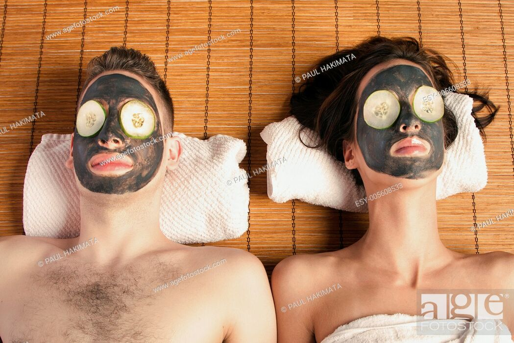 Stock Photo: Couples holiday retreat at spa getting facial mask with cucumber skincare relaxing beauty treatment on bamboo.