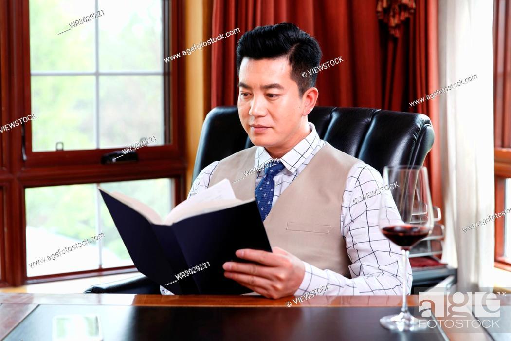 Stock Photo: The business man reads in the study.
