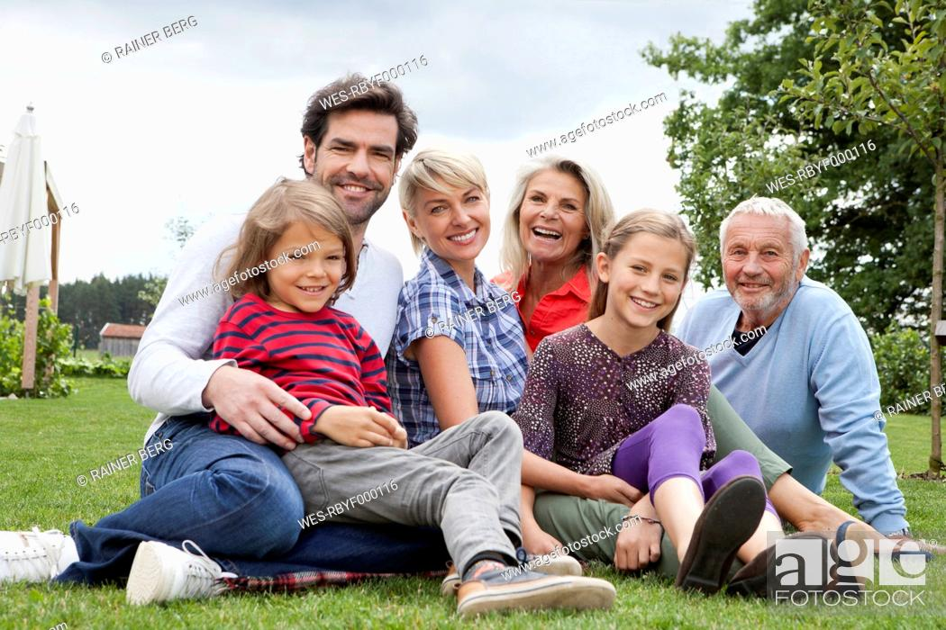 Stock Photo: Germany, Bavaria, Nuremberg, Family sitting in grass, smiling, portrait.