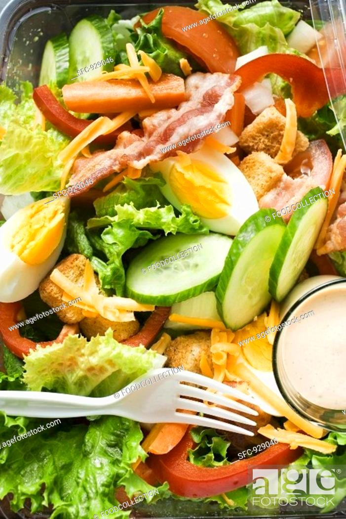 Stock Photo: Salad leaves with egg, cheese, bacon and dressing to take away.