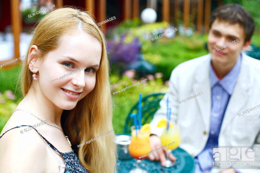 Stock Photo: Portrait of a young woman smiling with a young man sitting with her.
