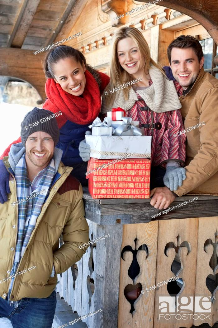 Stock Photo: Portrait of smiling couples with Christmas gifts on cabin porch.