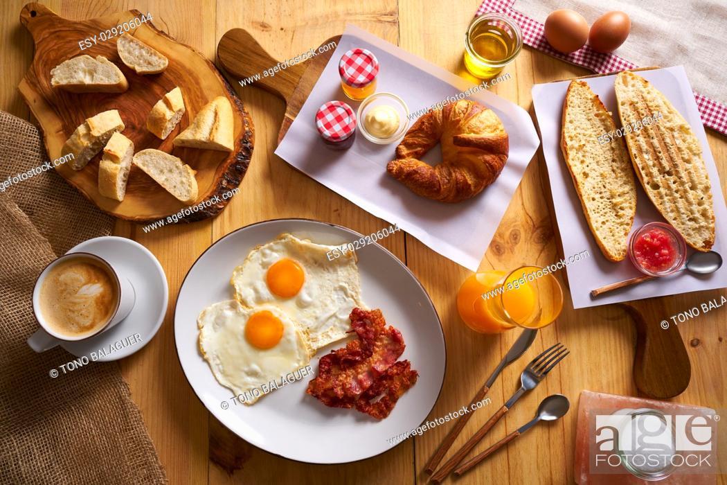 Imagen: Continental breakfast croissant eggs bacon bread slices orange jiuce.