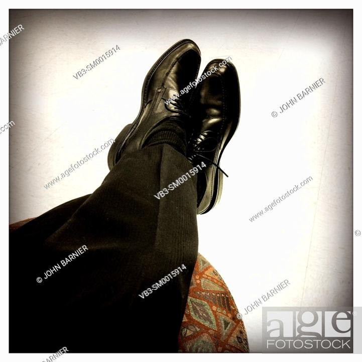Stock Photo: Crossed legs with black dress shoes and pants put up onto a footstool.
